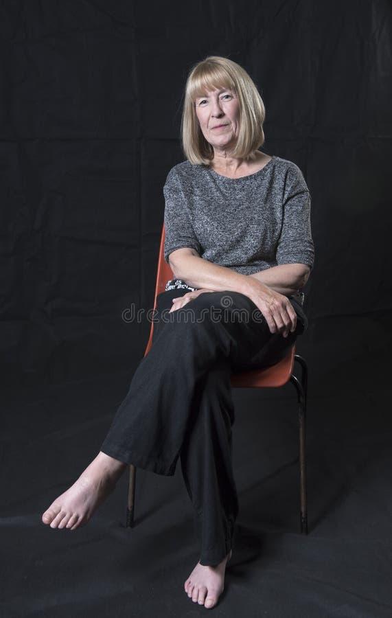 Mogen blond kvinna med ett allvarligt ansiktsuttryck royaltyfri fotografi