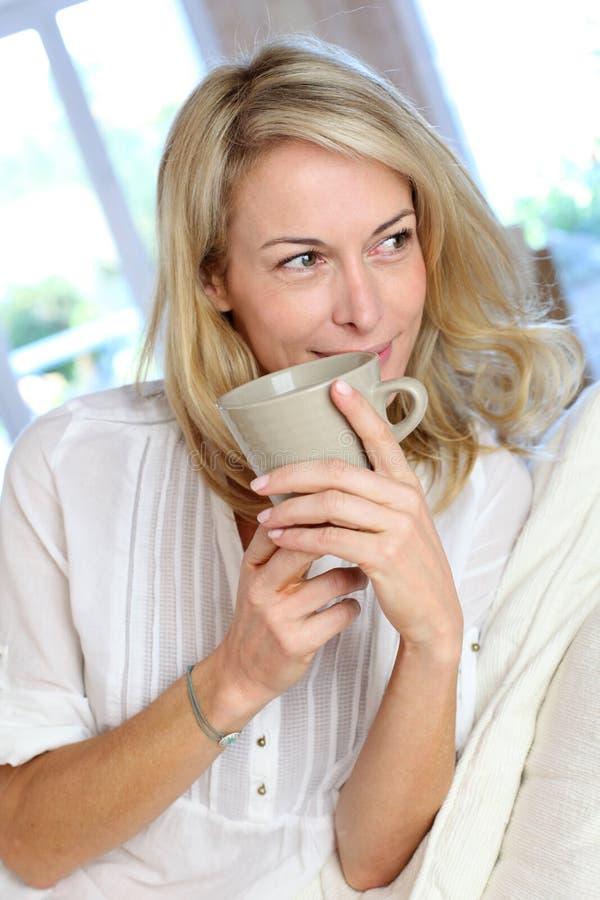 Mogen blond kvinna med kopp te royaltyfri fotografi