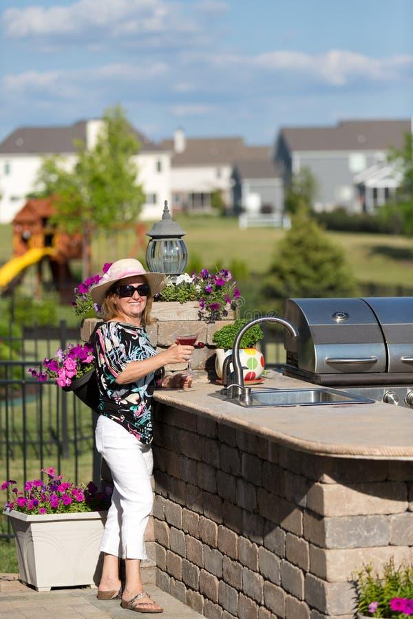 Mogen blond kvinna som har Martini utomhus royaltyfri bild