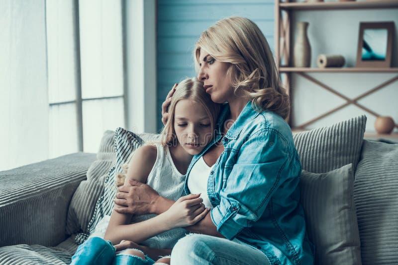 Mogen blond kvinna som kramar den frustrerade dottern Begrepp av försoning av modern med dottern royaltyfri fotografi