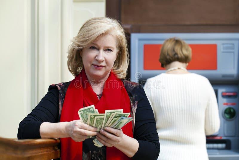 Mogen blond kvinna som räknar pengar nära ATM royaltyfria bilder