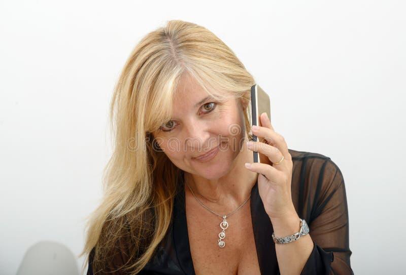 Mogen blond kvinna som talar på mobiltelefonen arkivbild