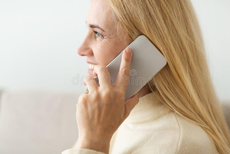 Mogen blond kvinna som talar p? telefonen, sidosikt fotografering för bildbyråer