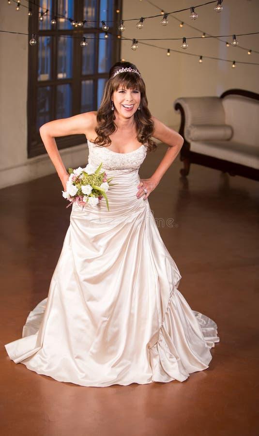 Mogen brud som skrattar i den vita klänningen royaltyfri foto