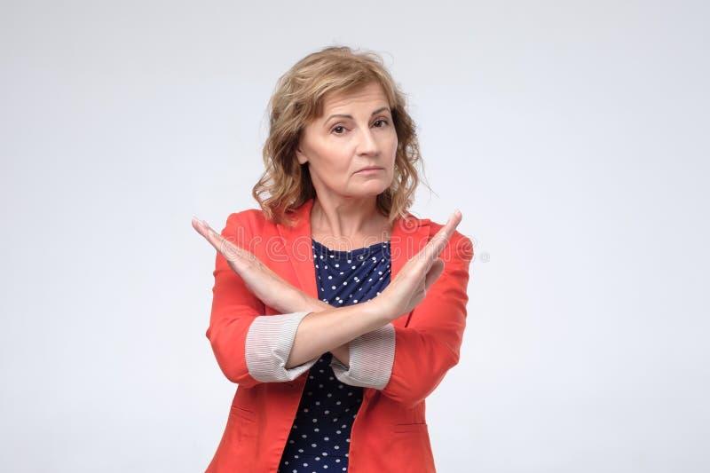 Mogen caucasian kvinna som rynkar pannan korsa armar på bröstkorg i kassering och att förbjuda gest arkivfoto