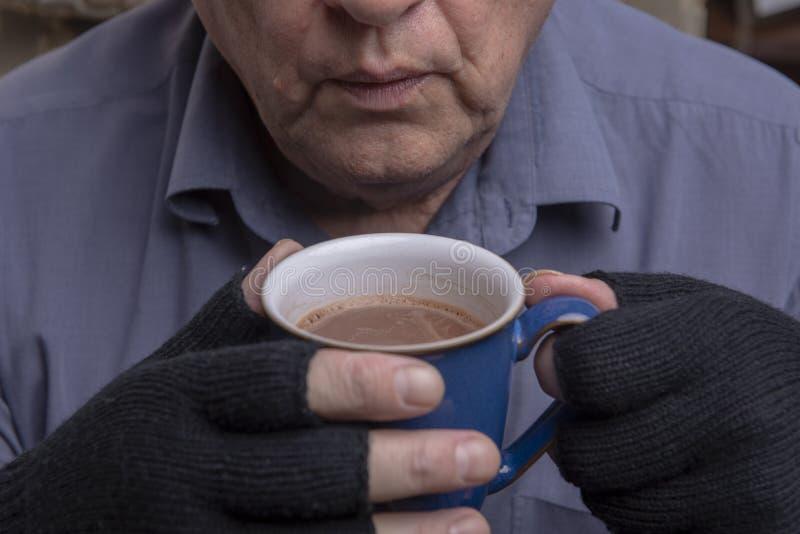 Mogen Caucasian man som griper en varm drink royaltyfri foto