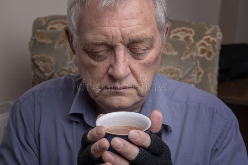Mogen Caucasian man som griper en varm drink arkivbild