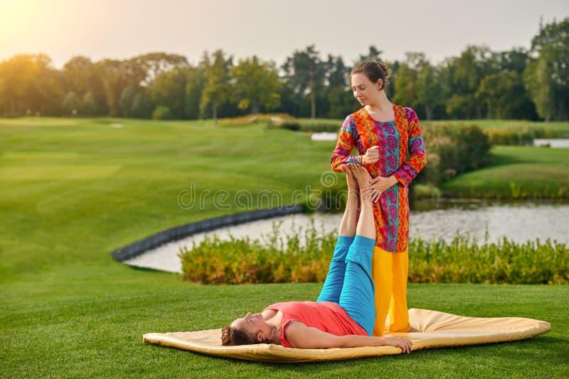 Mogen dam som får traditionell thai sträckande massage av terapeuten fotografering för bildbyråer