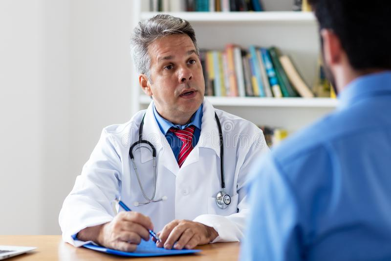 Mogen doktor som förklarar terapi till patienten arkivbilder