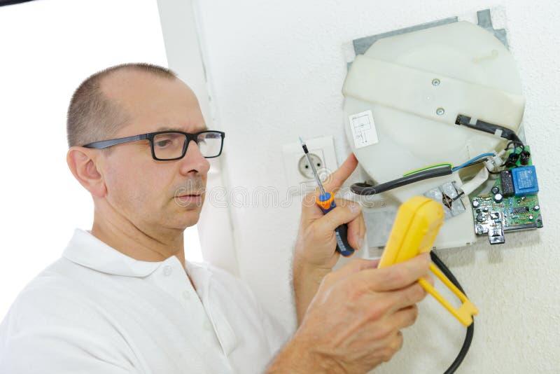 Mogen elektriker som arbetar med kablar och trådar royaltyfria foton