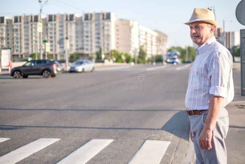 Mogen europeisk man som väntar för att korsa gatan fotografering för bildbyråer