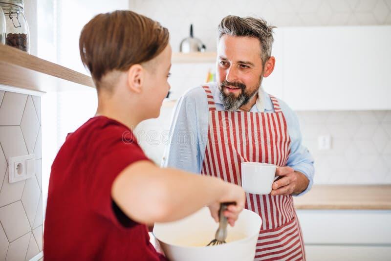 Mogen fader med den lilla sonen inomhus i kök som gör pannkakor royaltyfri bild