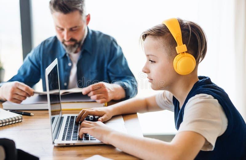Mogen fader med den lilla sonen som inomhus sitter på tabellen, genom att använda hörlurar och bärbara datorn royaltyfria bilder