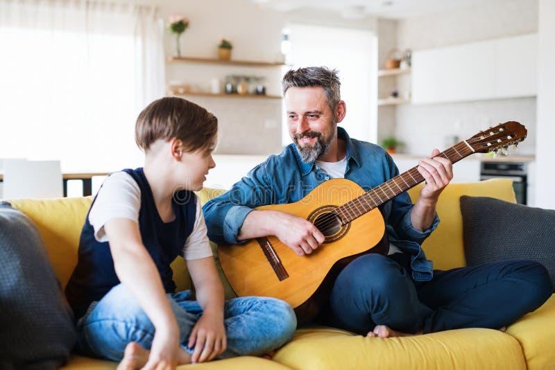 Mogen fader med den lilla sonen som inomhus sitter p? soffan och att spela gitarren arkivfoto