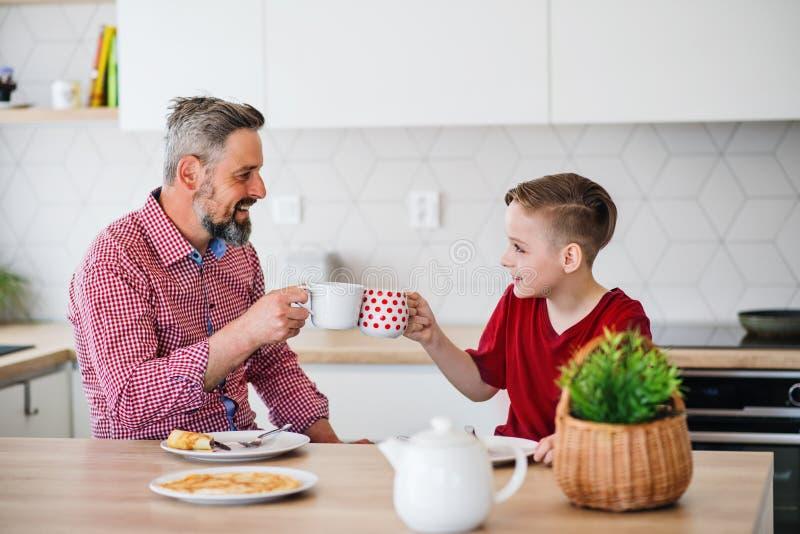 Mogen fader med den lilla sonen som sitter inomhus på tabellen som äter pannkakor royaltyfri bild