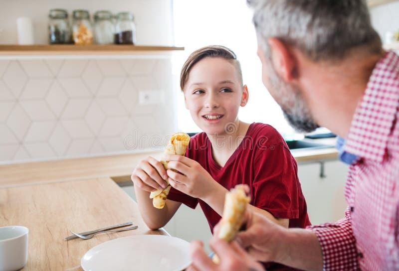 Mogen fader med den lilla sonen som sitter inomhus på tabellen som äter pannkakor royaltyfria foton