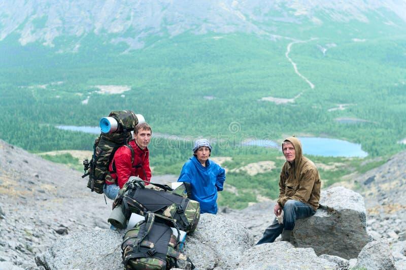 Mogen fader, moder och son som tillsammans fotvandrar i berg arkivbilder