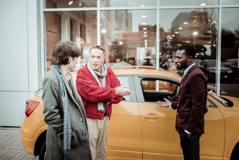 Mogen fader som talar till hans unga son, medan köpa bilen för honom royaltyfri fotografi