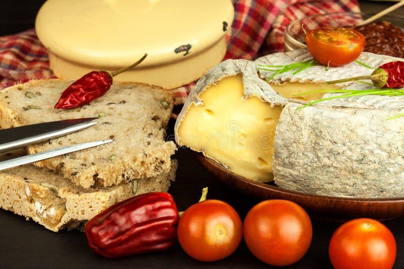 Mogen formost för hemhjälp med tomater Isolerade objekt Aromatisk ost med formen arkivbild