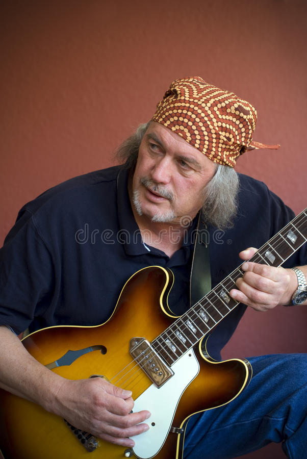 Mogen gitarrist med gitarren och bandanaen royaltyfria bilder
