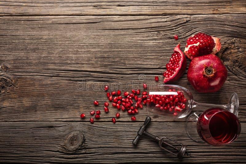 Mogen granatäpplefrukt med ett exponeringsglas av vin och en korkskruv på en träbakgrund royaltyfri bild