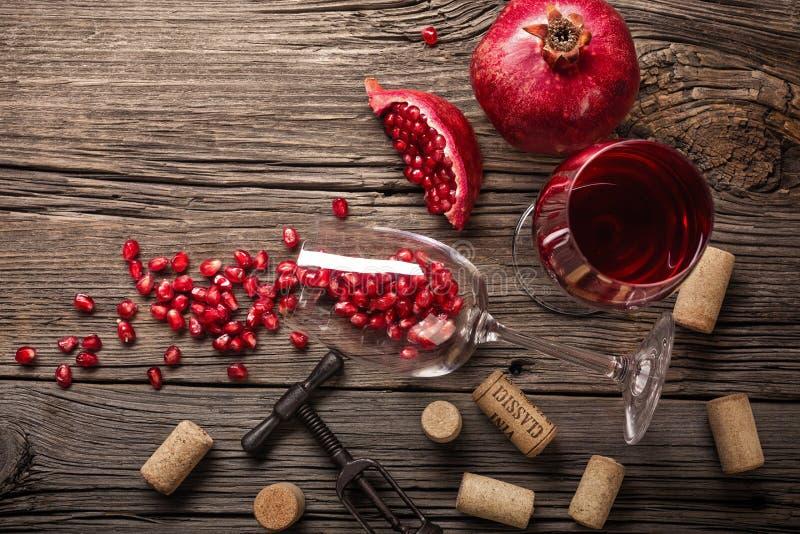 Mogen granatäpplefrukt med ett exponeringsglas av vin och en korkskruv på en träbakgrund arkivfoto