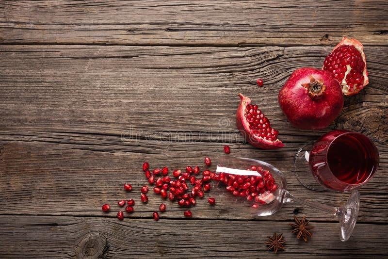 Mogen granat?pplefrukt med ett exponeringsglas av vin och en korkskruv p? en tr?bakgrund arkivfoto