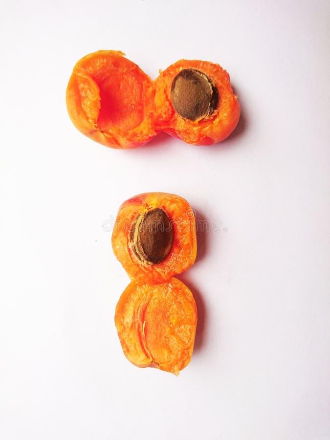 Mogen gul bruten aprikos på en vit bakgrund royaltyfri bild