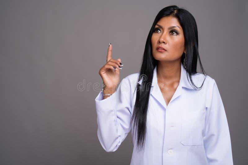Mogen härlig asiatisk kvinnadoktor mot grå bakgrund royaltyfri fotografi