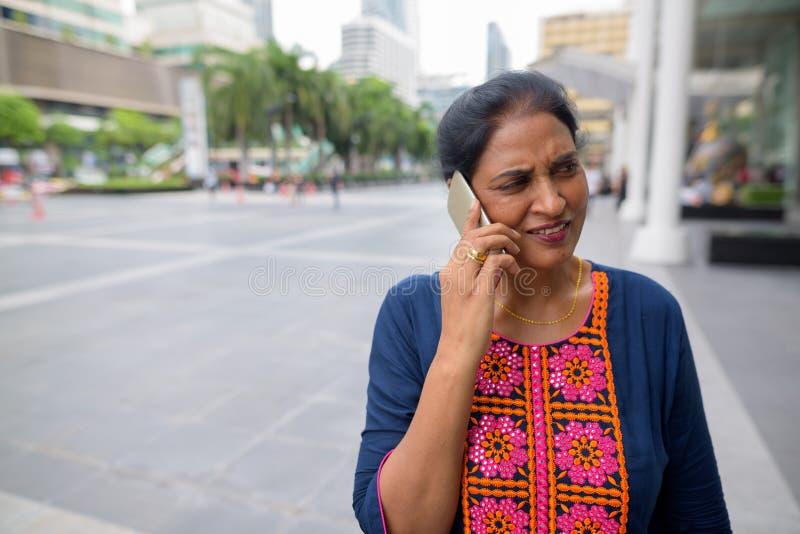 Mogen härlig indisk kvinna som talar på telefonen i stad arkivfoton