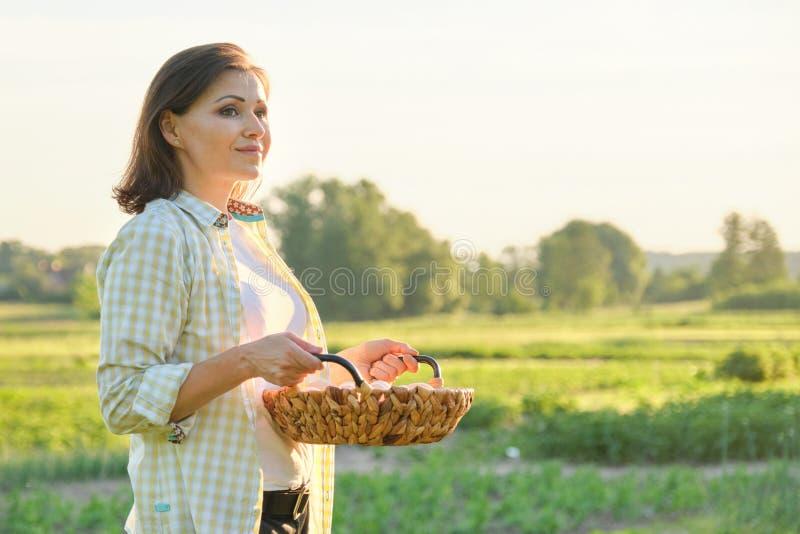 Mogen härlig kvinnabonde med korgen av nya ägg arkivbild