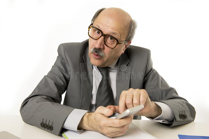 Mogen hög affärsman för proper och rumsren 60-tal som använder mobiltelefonen på att arbeta för kontorsskrivbord som är lyckligt, fotografering för bildbyråer