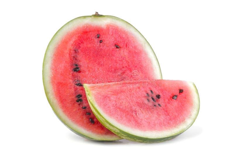 mogen halva av en vattenmelon och en skiva bredvid en vit bakgrund isolerat royaltyfri fotografi