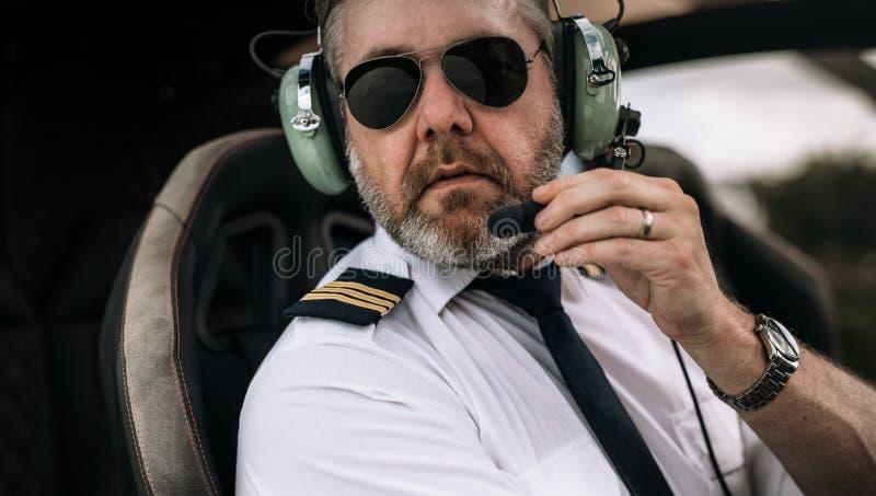Mogen helikopterpilot med hörlurar med mikrofon arkivfoton
