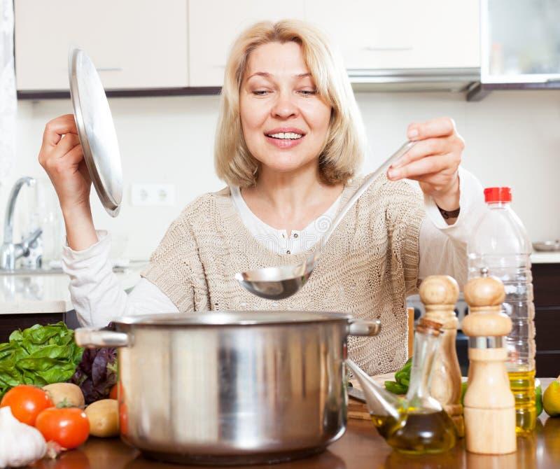Mogen hemmafru med slevmatlagningsoppa i panna i hem- kök royaltyfri fotografi