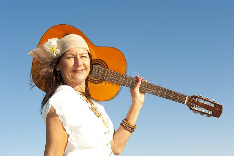 Mogen hippiekvinna med gitarren arkivbilder
