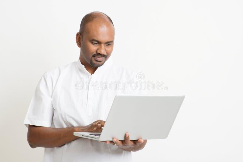 Mogen indisk man som använder bärbara datorn arkivbilder