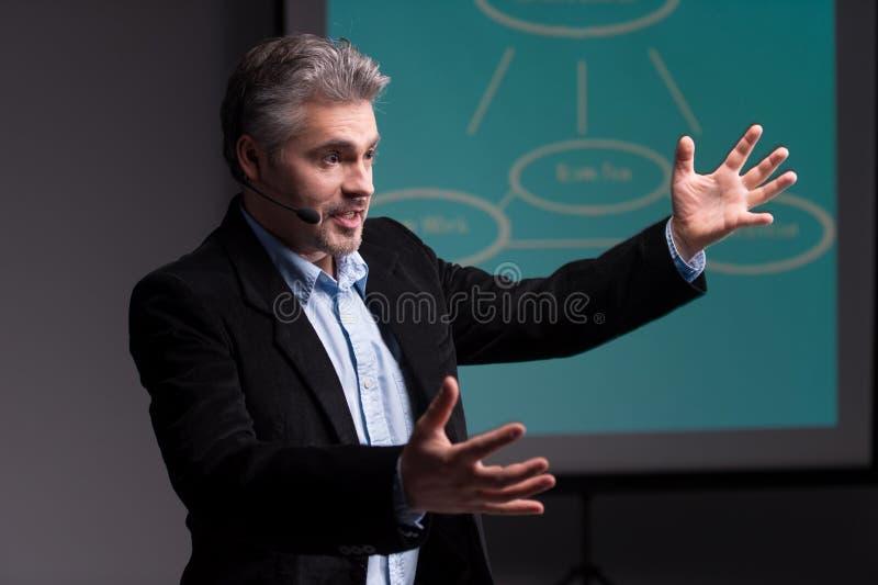 Mogen instruktör som gör en gest för skärm med presentation arkivfoto
