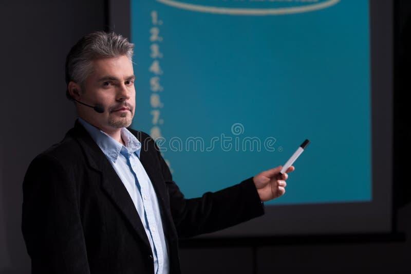 Mogen instruktör som pekar på skärmen med presentation royaltyfria foton