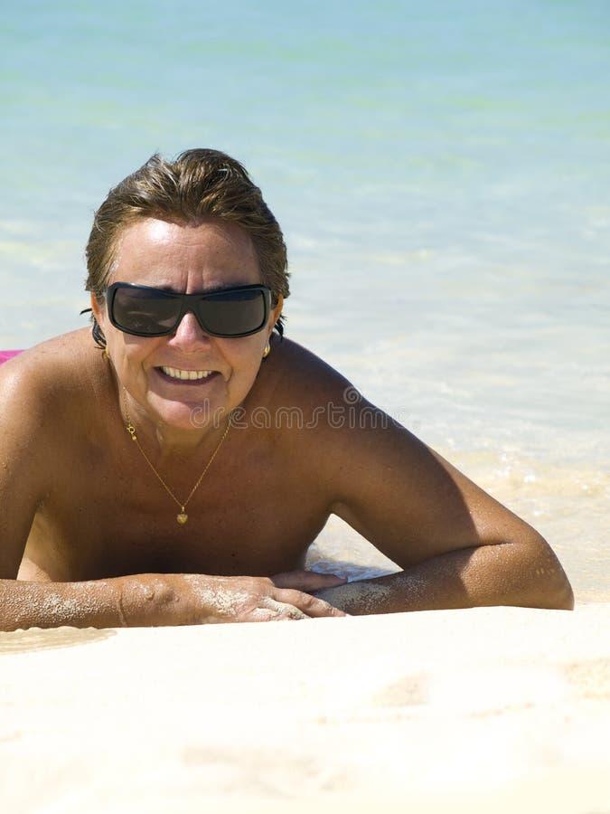 mogen kvinna för strand arkivfoto
