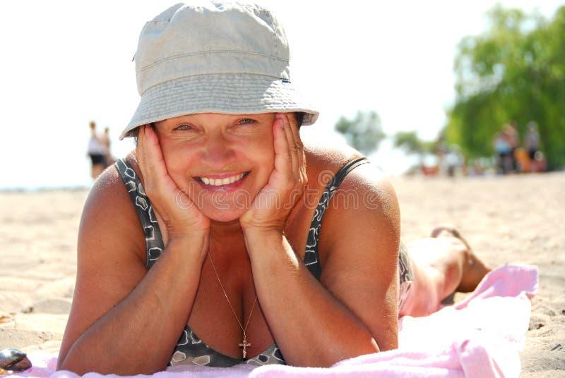 mogen kvinna för strand arkivbild