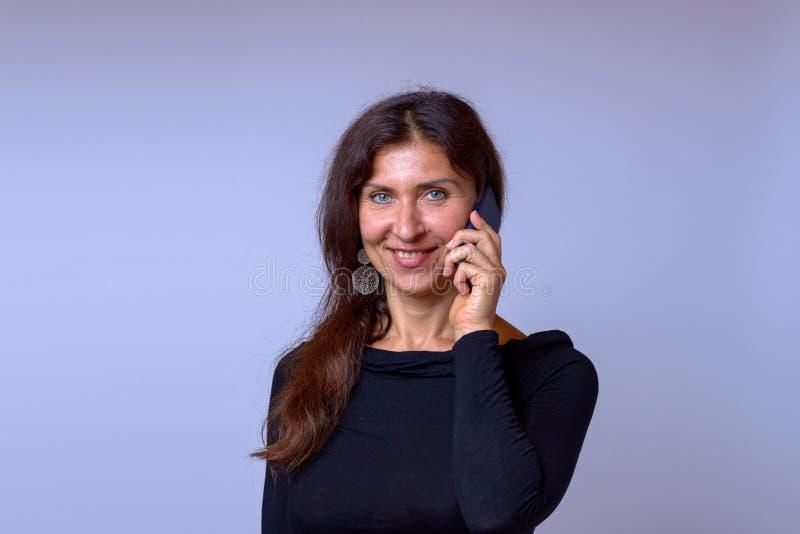Mogen kvinna för vänskapsmatch som talar på mobiltelefonen arkivbild
