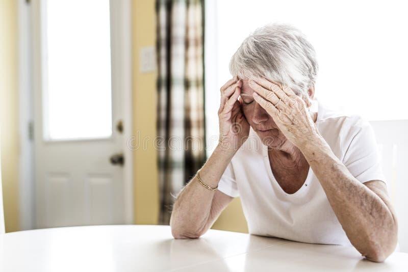 Mogen kvinna hemma som trycker på hennes huvud med henne händer, medan ha en huvudvärk smärta arkivbild