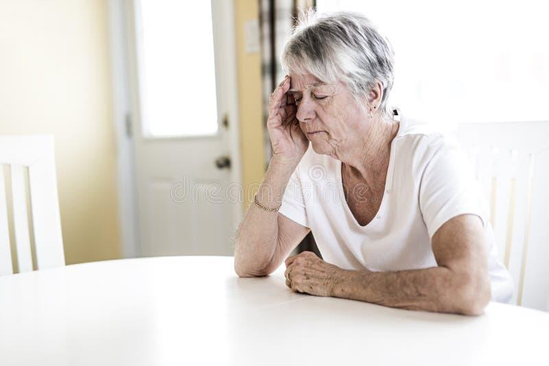 Mogen kvinna hemma som trycker på hennes huvud med henne händer, medan ha en huvudvärk smärta arkivfoto