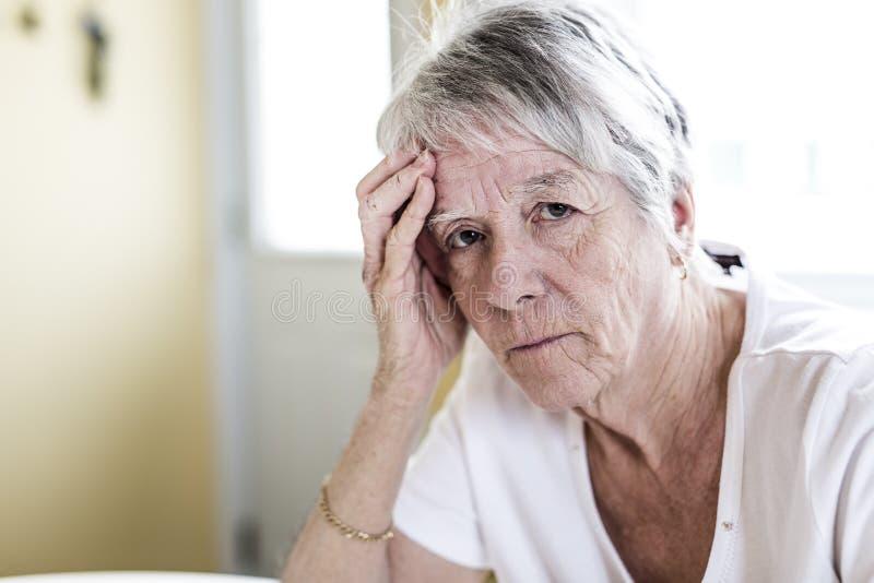 Mogen kvinna hemma som trycker på hennes huvud med henne händer, medan ha en huvudvärk smärta royaltyfria foton