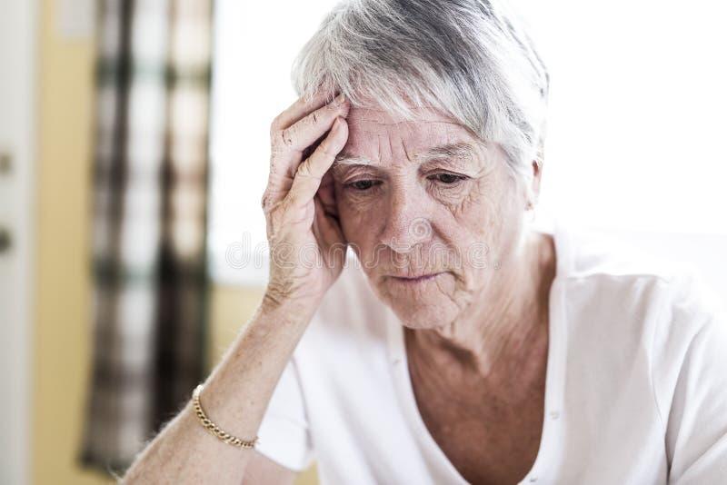 Mogen kvinna hemma som trycker på hennes huvud med henne händer, medan ha en huvudvärk smärta royaltyfri fotografi