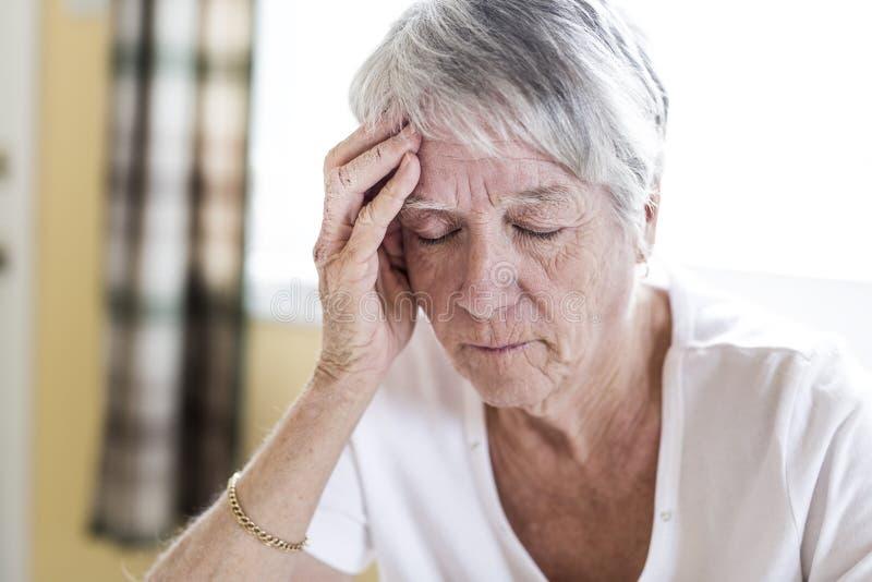 Mogen kvinna hemma som trycker på hennes huvud med henne händer, medan ha en huvudvärk smärta arkivbilder