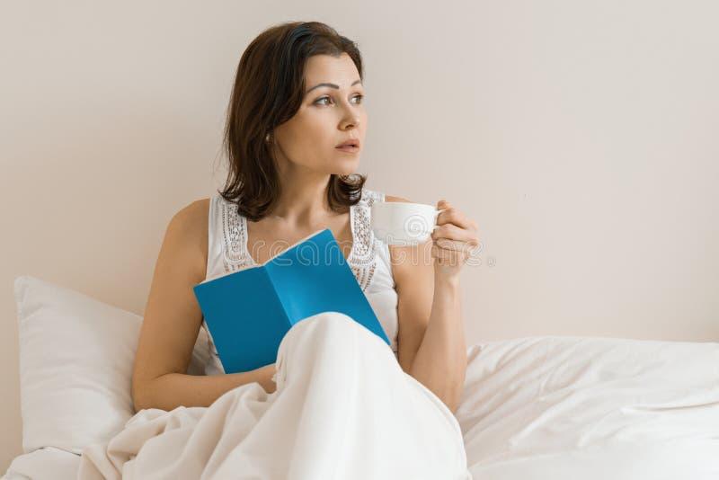 Mogen kvinna hemma som vilar i säng med en kopp av nytt morgonkaffe och läser en bok Kvinnliga blickar i profil arkivfoton