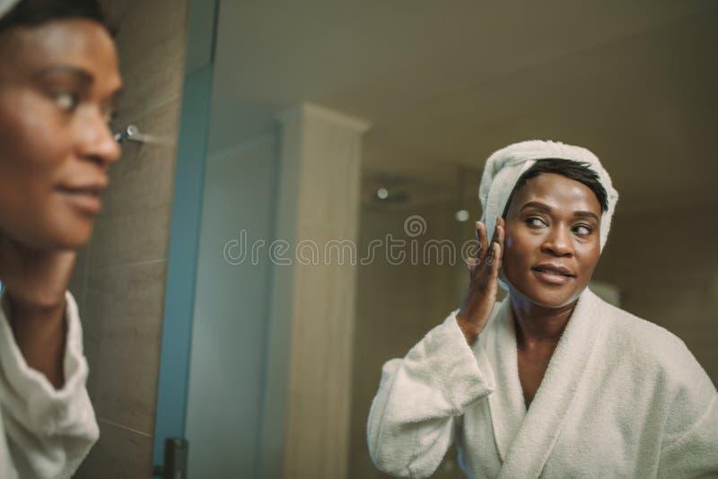 Mogen kvinna i badrocken som sätter på kräm på hennes framsidahud royaltyfri bild