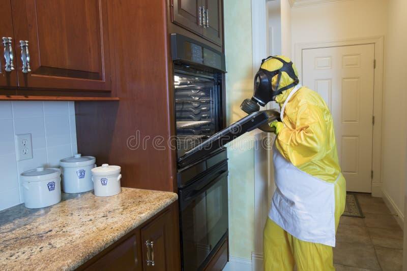 Mogen kvinna i dörr för ugn för Haz matt dräktöppning arkivbild